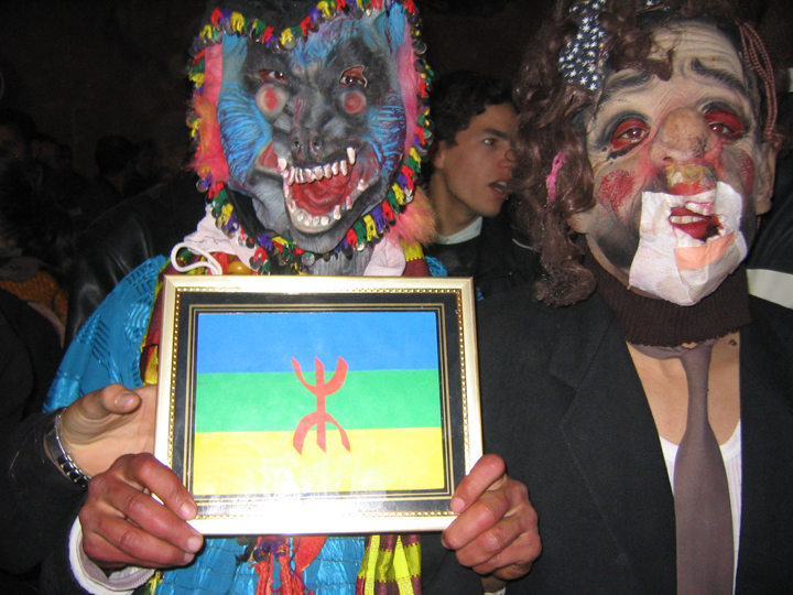 "Udayen Tashurt  Jewish Ashoura) masquerade festival, with an Amazigh activist dressed up as a ""Jew""  and displaying an Amazigh flag; Goulmima, Morocco, mid-2000s. Photo by author."